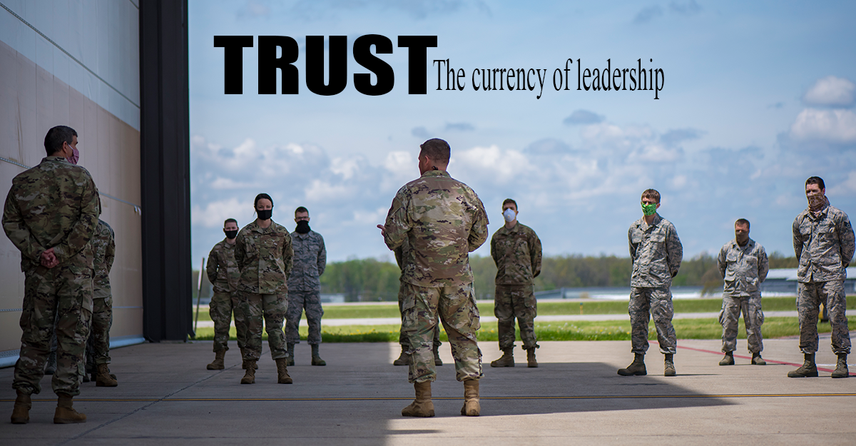 TRUST: The currency of leadership. BG Camp addressesgroup of airmen outside, social distancing, wearing ppe.