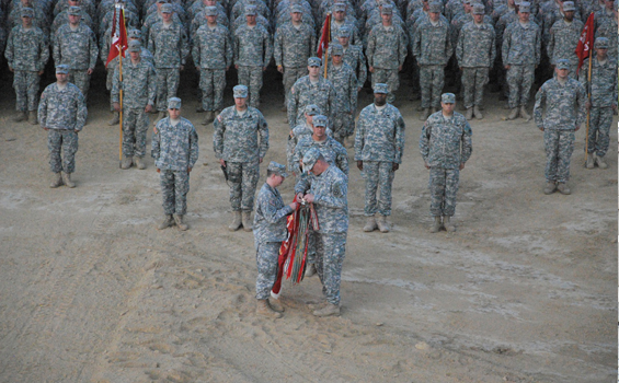 Lt. Col. Tom Caldwell (foreground, left) commander of the 216th Engineer Battalion, and Battalion Command Sgt. Maj. Steven Shepherd affix a campaign streamer to the battalion's organizational colors June 15, 2011