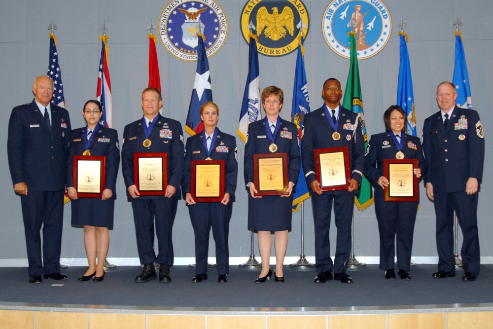Airmen of the year stand on stage with awards.
