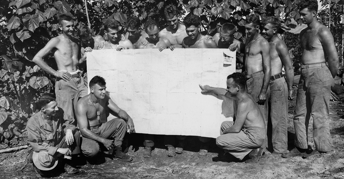 Shirtless Soldiers stand around large greeting card.