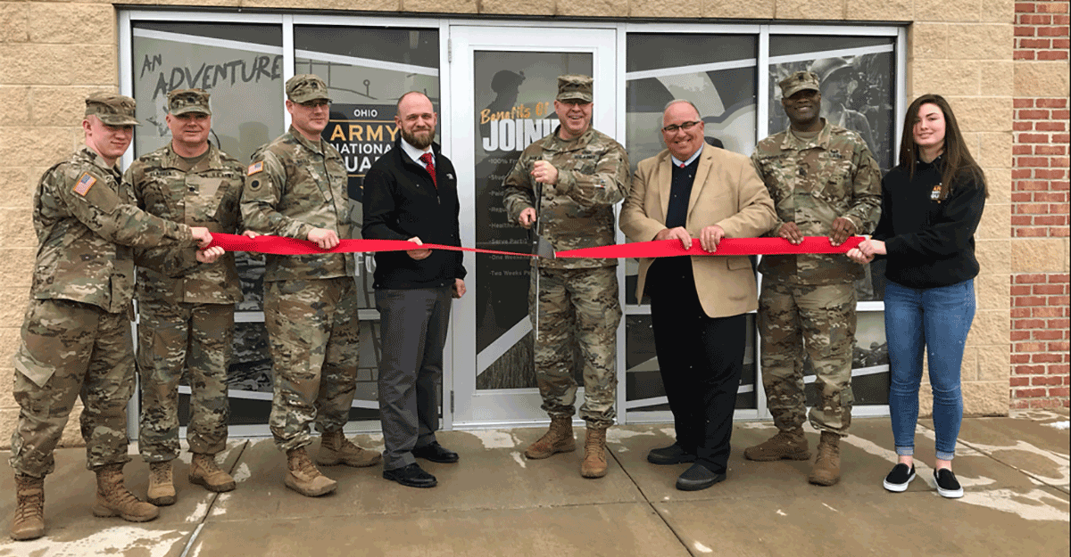 Soldiers, leaders, and officials with ribbon in front of doors to recruiting office