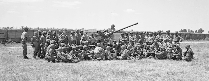 Soldiers from the 137th AAA Bn. receive a class on a 40 mm anti-aircraft gun.