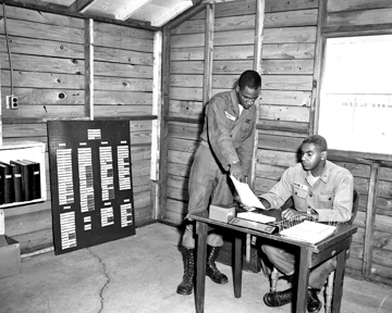Pvt. Lipkin shows paper work to Cpt. James B. Payne of the 137th AAA Bn.