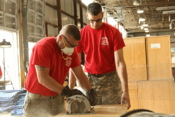 An Ohio Army National Guard Warrant Officer Candidate School student saws off excess material while his classmate steadies the wood.