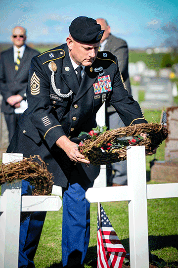 Soldier places wreath on cross monument.