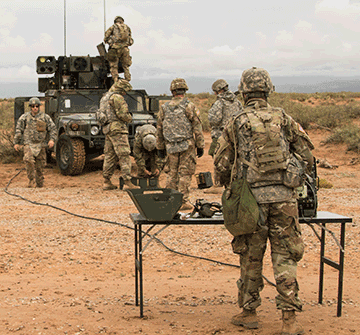 Soldiers stand around a vehicle on missle range.