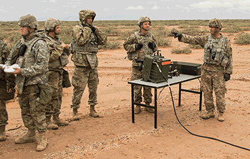 Soldiers stand around a table on missle range.
