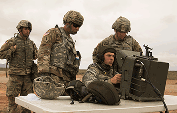 Four soldiers around a table on missle range looking at screen.