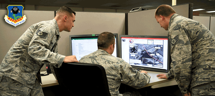 Three airmen galer around desk to look at computer screen.