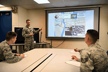 Airman at video screen, briefing 2 airmen sitting at table.