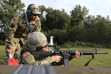 Soldier kneeling while shooting rifle while Soldier observes standing overtop.