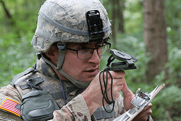 Closeup of Soldier looking at compass in forest.
