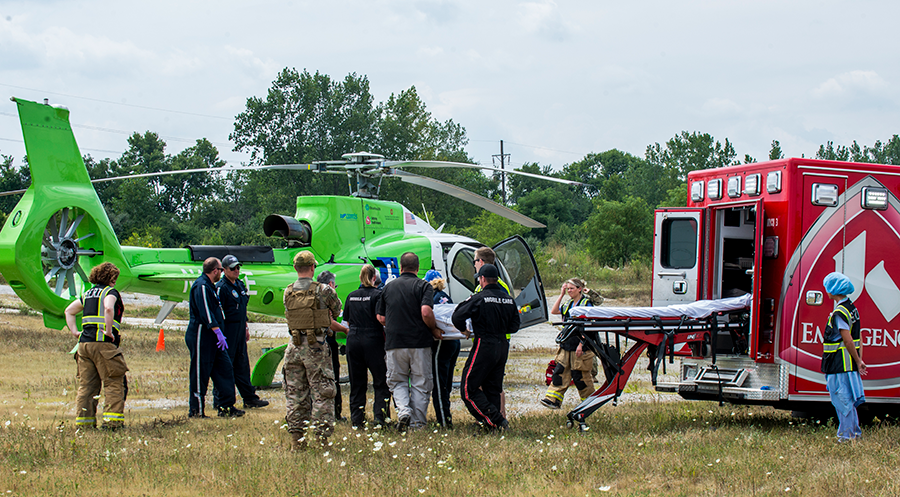 Soldiers and EMS transport simulated causuality from truck to helicopter.