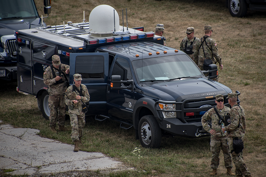 Soldiers exit emergency vehicle in field.
