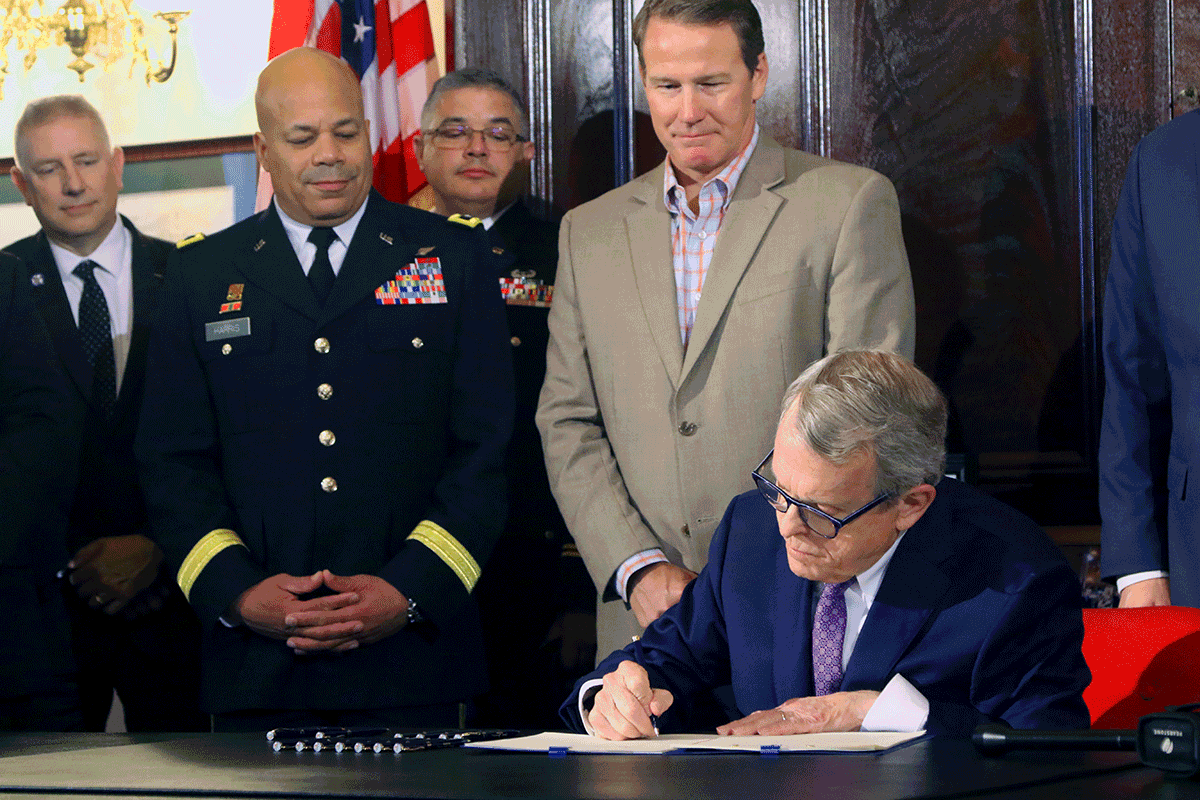 Cover of Buckey Guard online publication - Governor sits at desk signing while others stand around him.