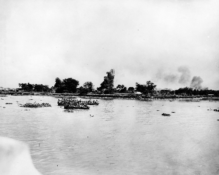 Soldiers in plywood assault boats across river.