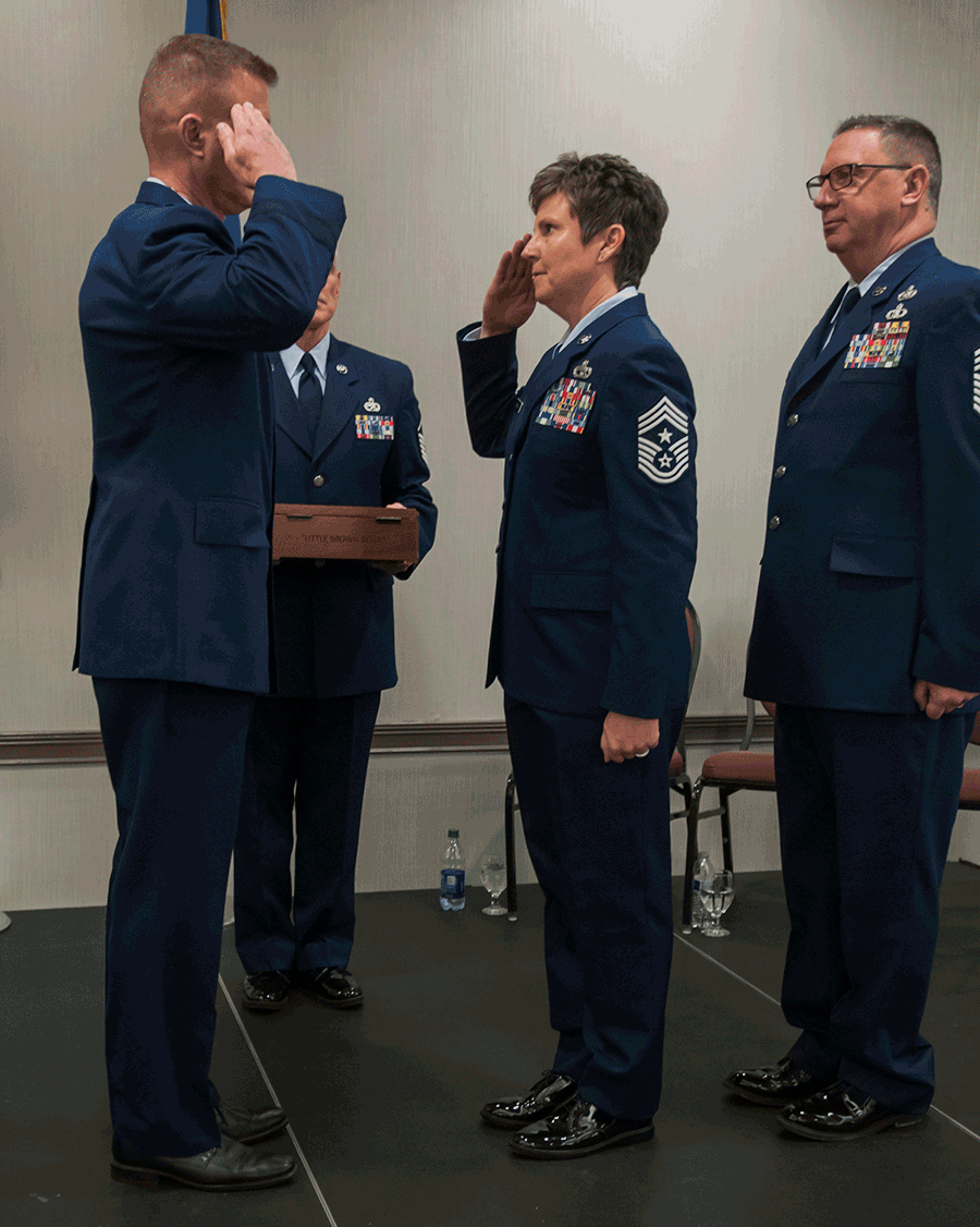 Chief Master Sgt. Heidi Bunker salutes Brig. Gen. Todd Audet with Chief Master Sgt. Thomas Jones.