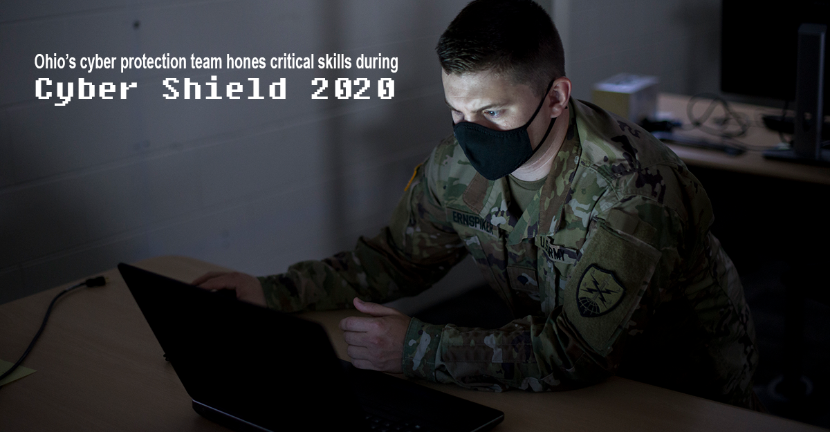 Soldier sits at laptop in dark.