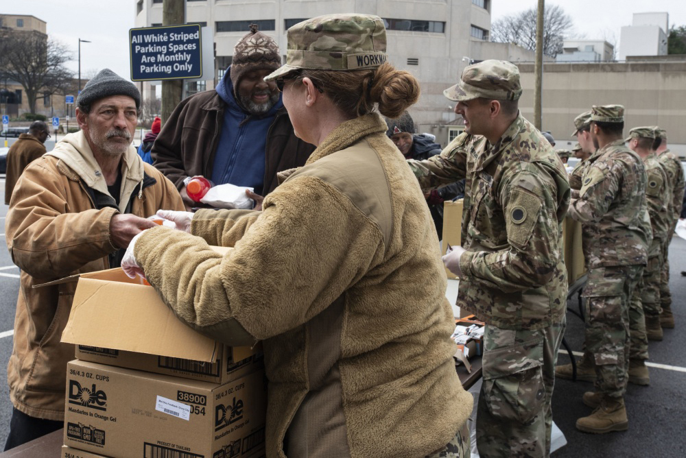 Soldiers hand dinners to citizens in need.