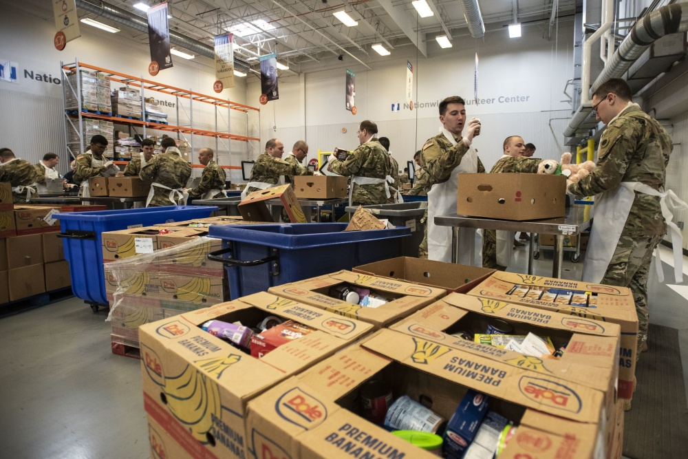 Soldiers load boxes in warehouse.