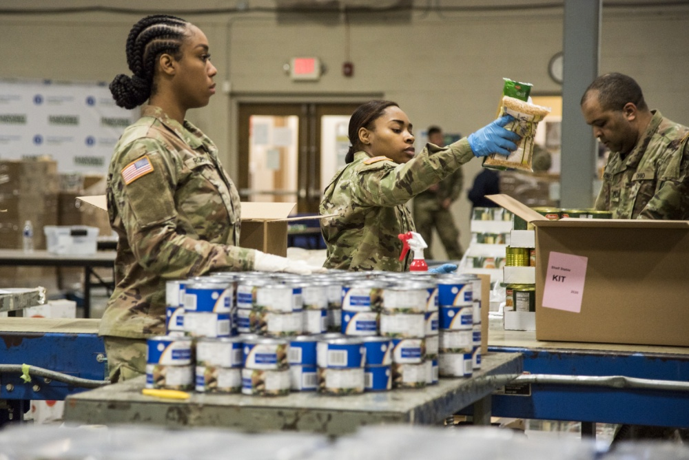 Soldiers load boxes with canned goods.