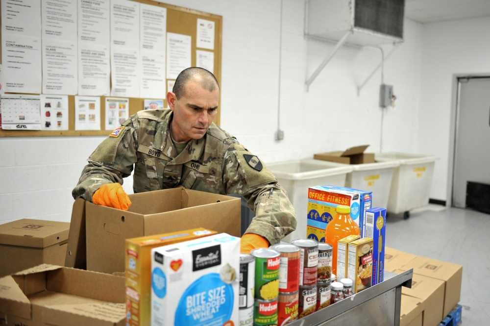 Soldier looks over chart in pantry