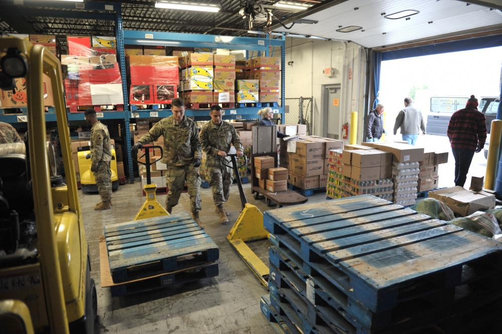 Soldiers load pallets inwarehouse.