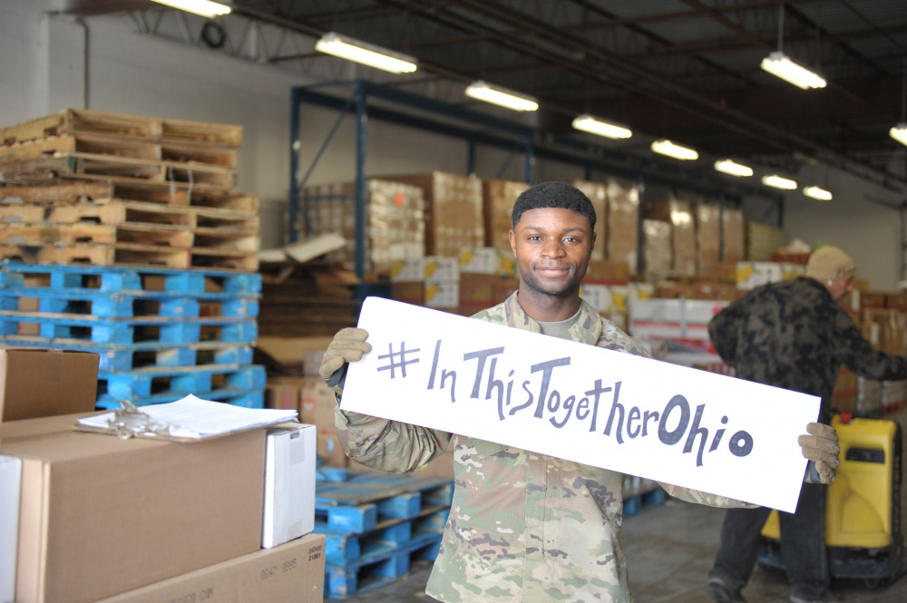 Soldier holds #InThisTogetherOhio sign in warehouse.