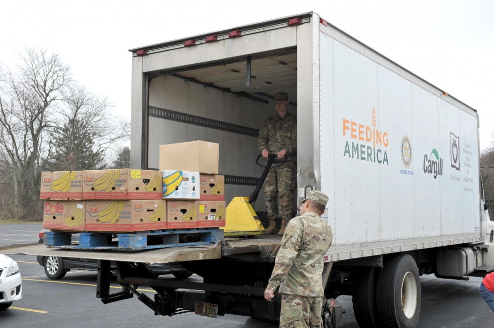 Soldiers unload semi-trailer.