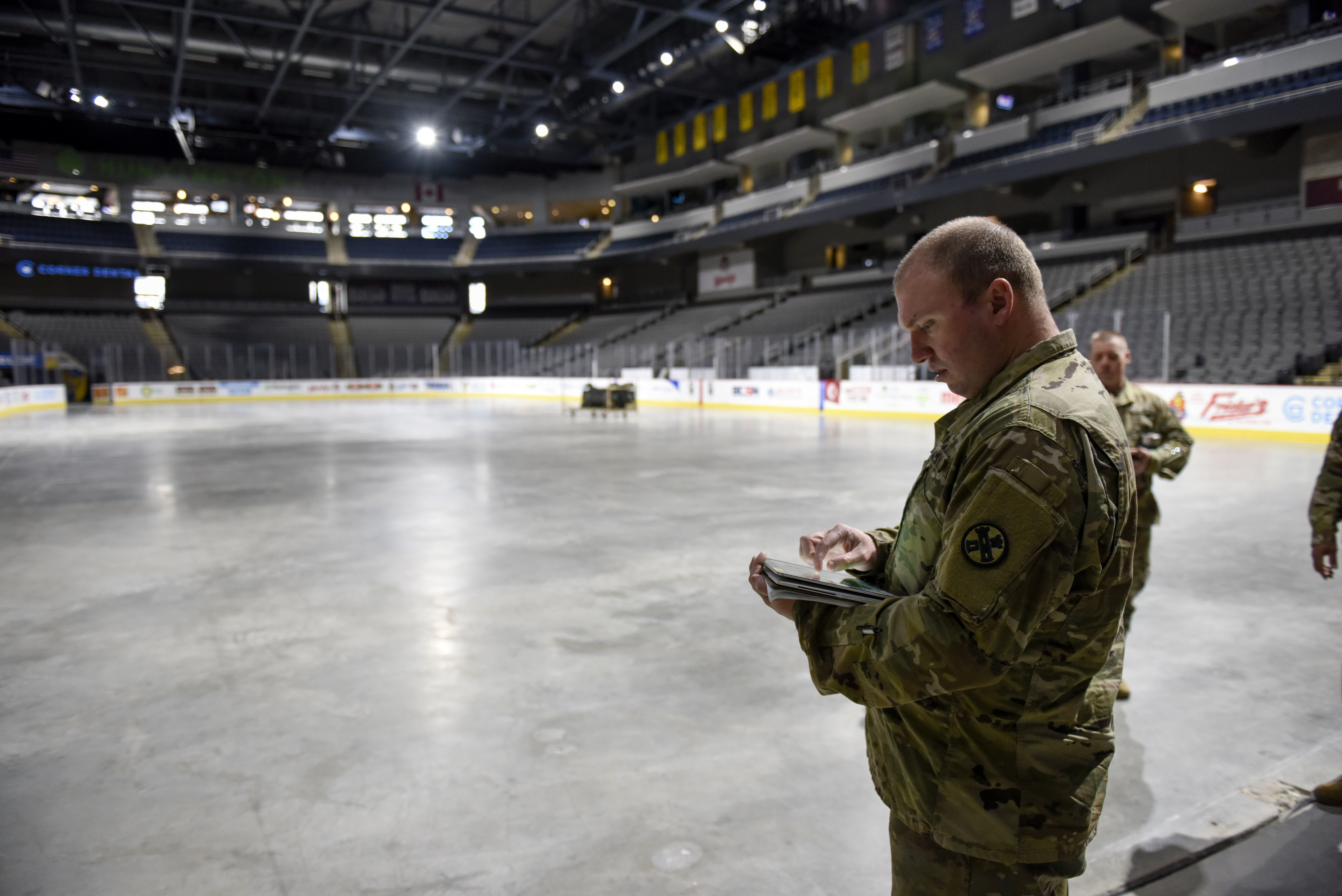 Guard members inputs info on hand-held device in hockey arena.