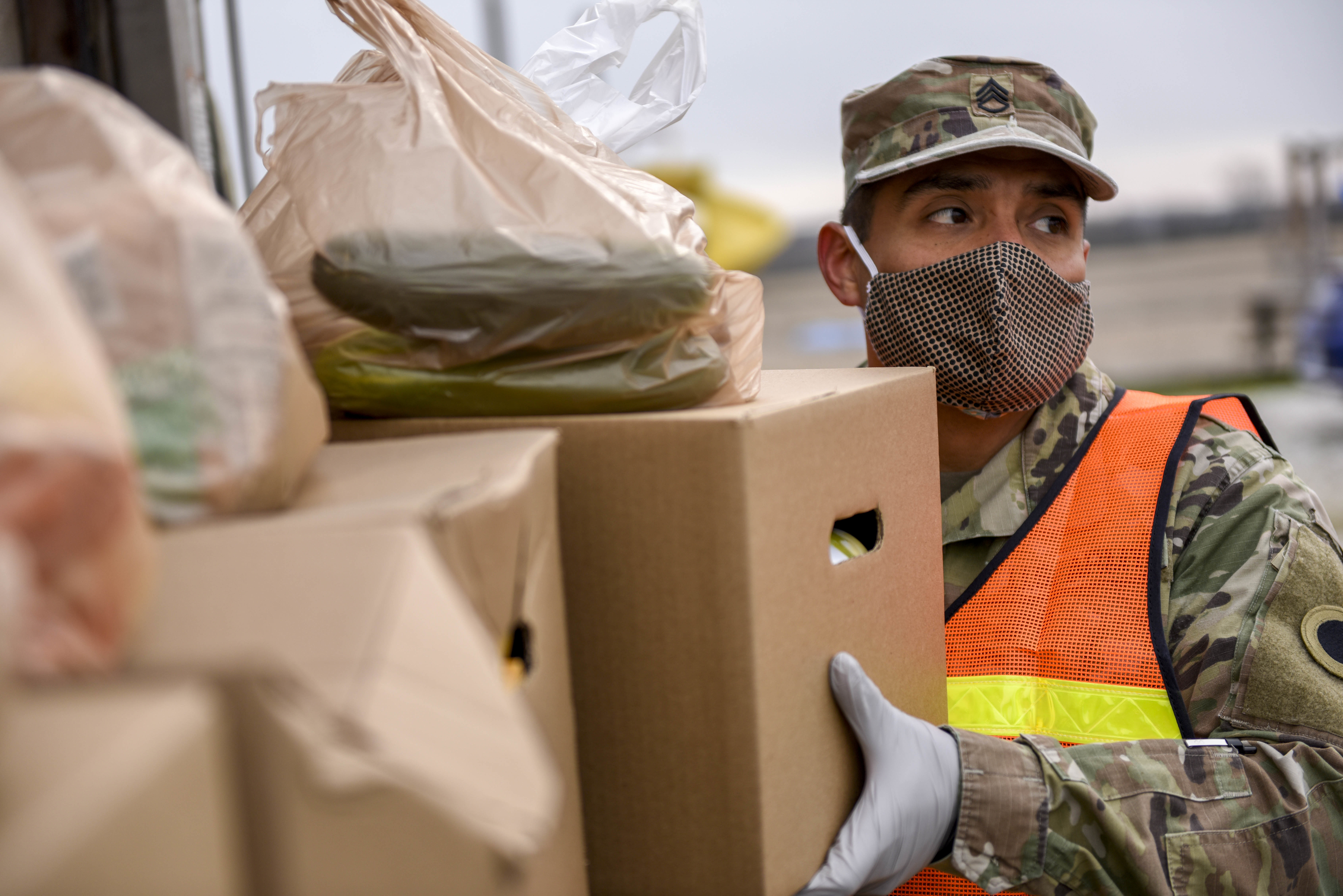 Soldiers unpack groceries at food bank.
