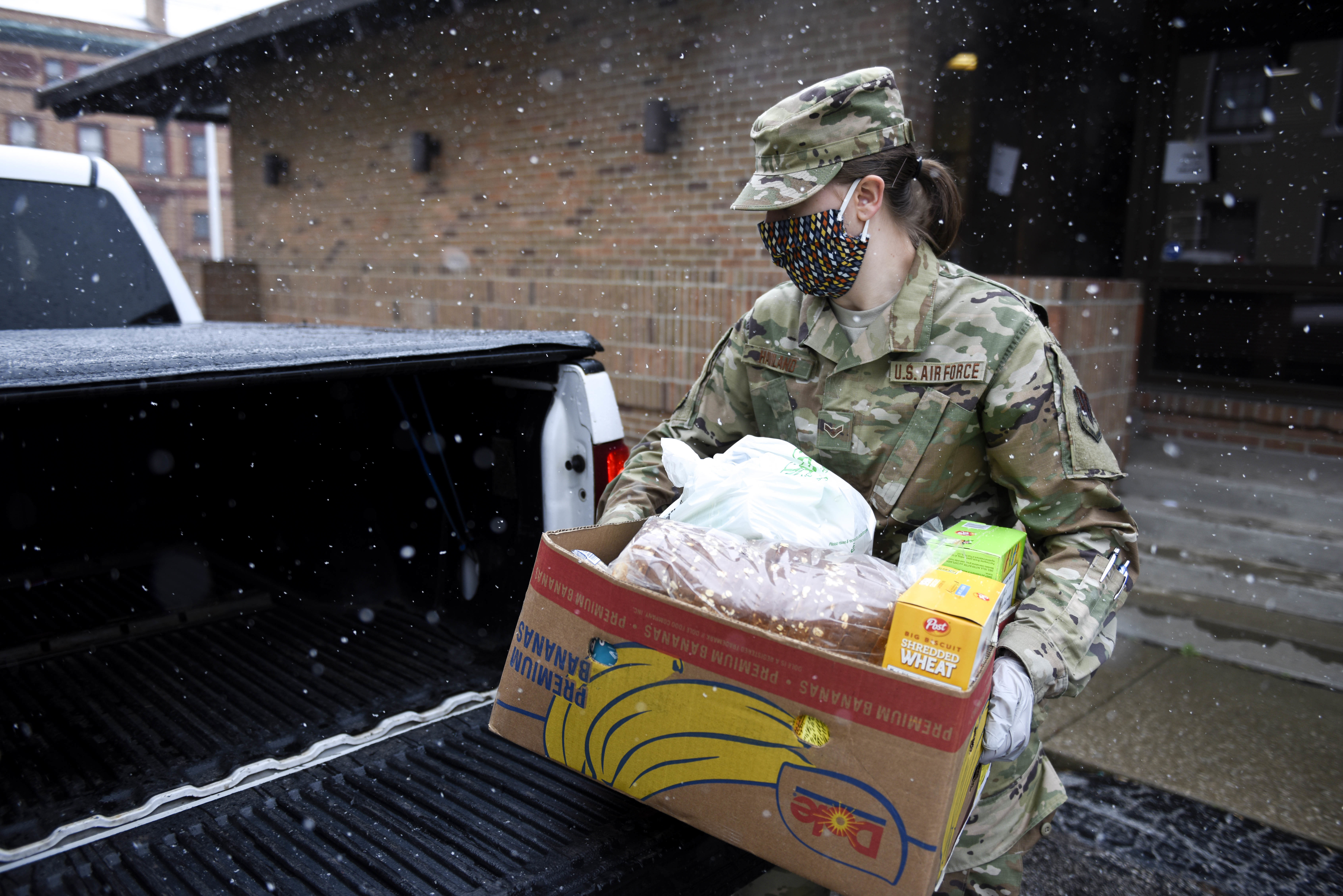 FEmale soldier loads box into back of a truck in the snow.