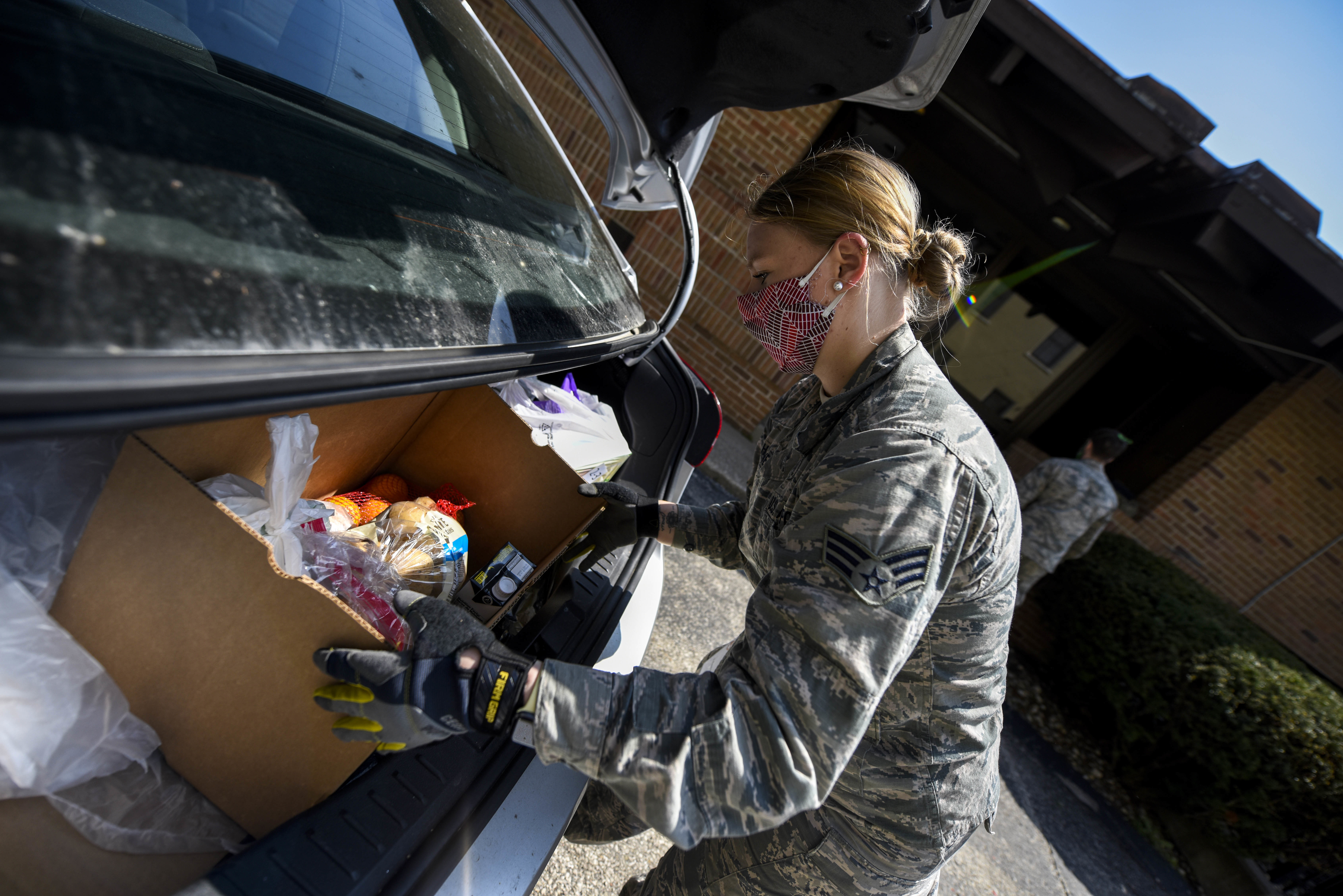 Female soldier loads grocercies into vehicle.