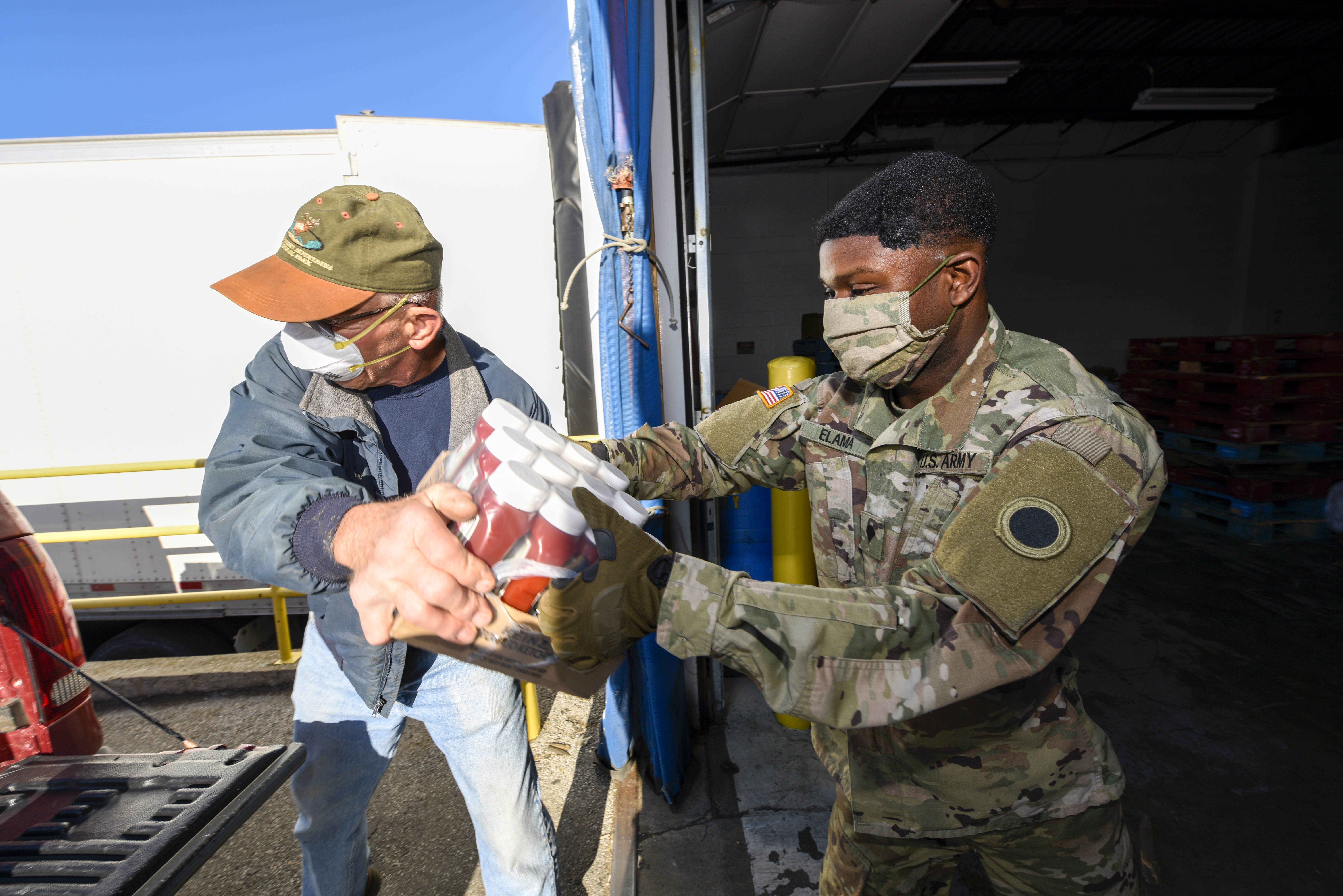 Soldier hands groceries to man to load in back of truck.