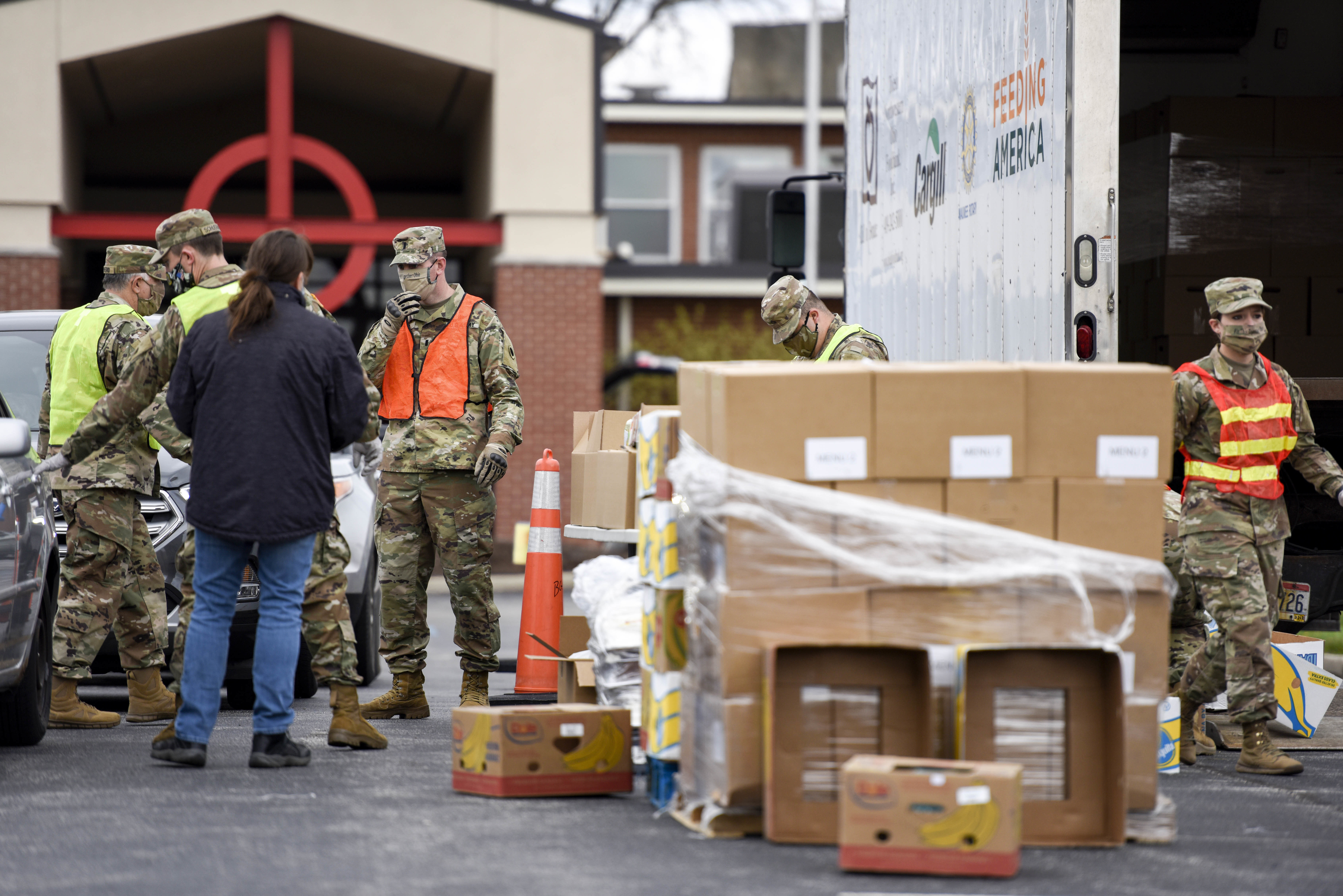 Soldiers gather boxes around semi trailer for distribution.