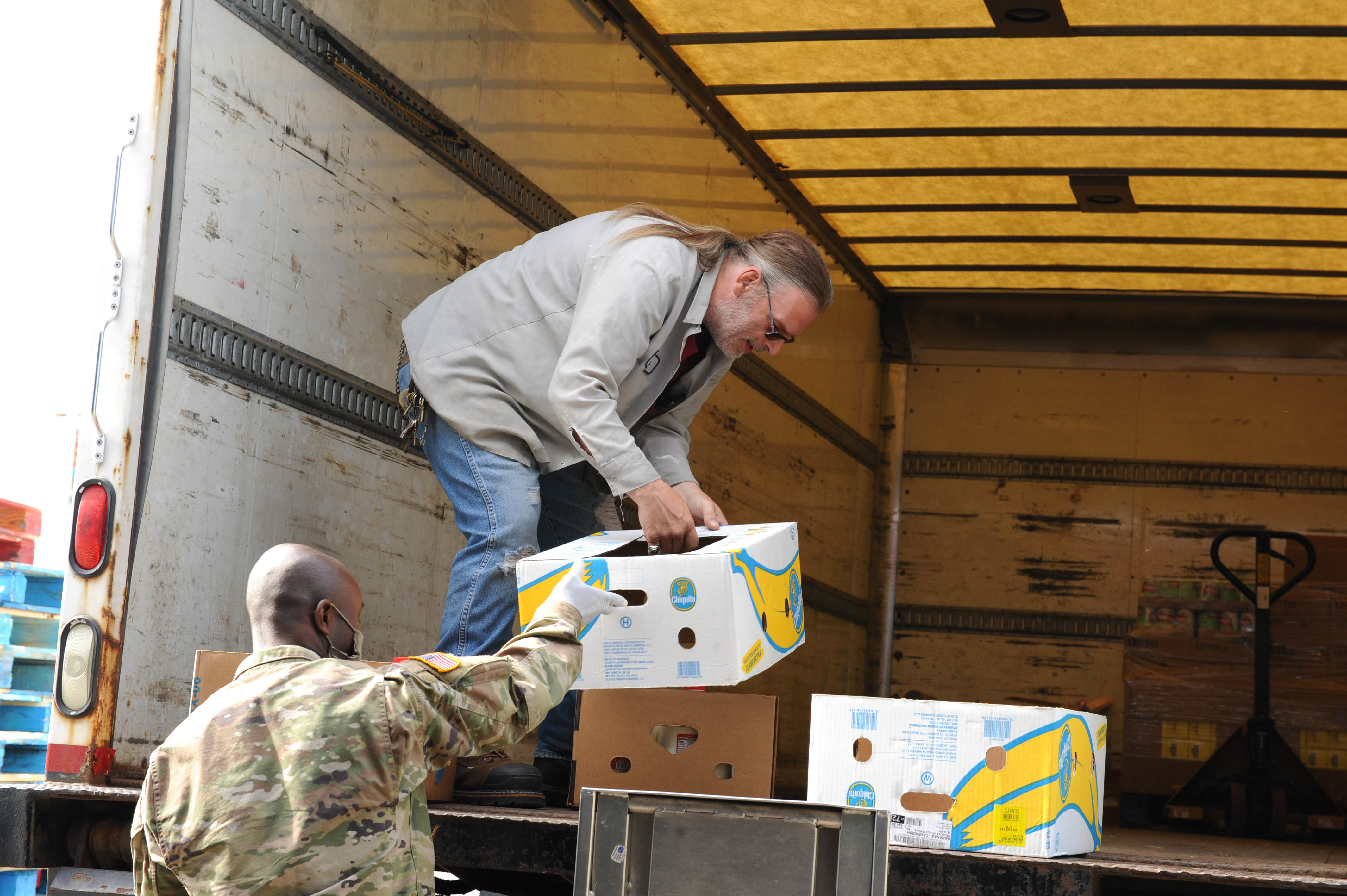 Soldier hands box of bananas to civilian helper in back of truck