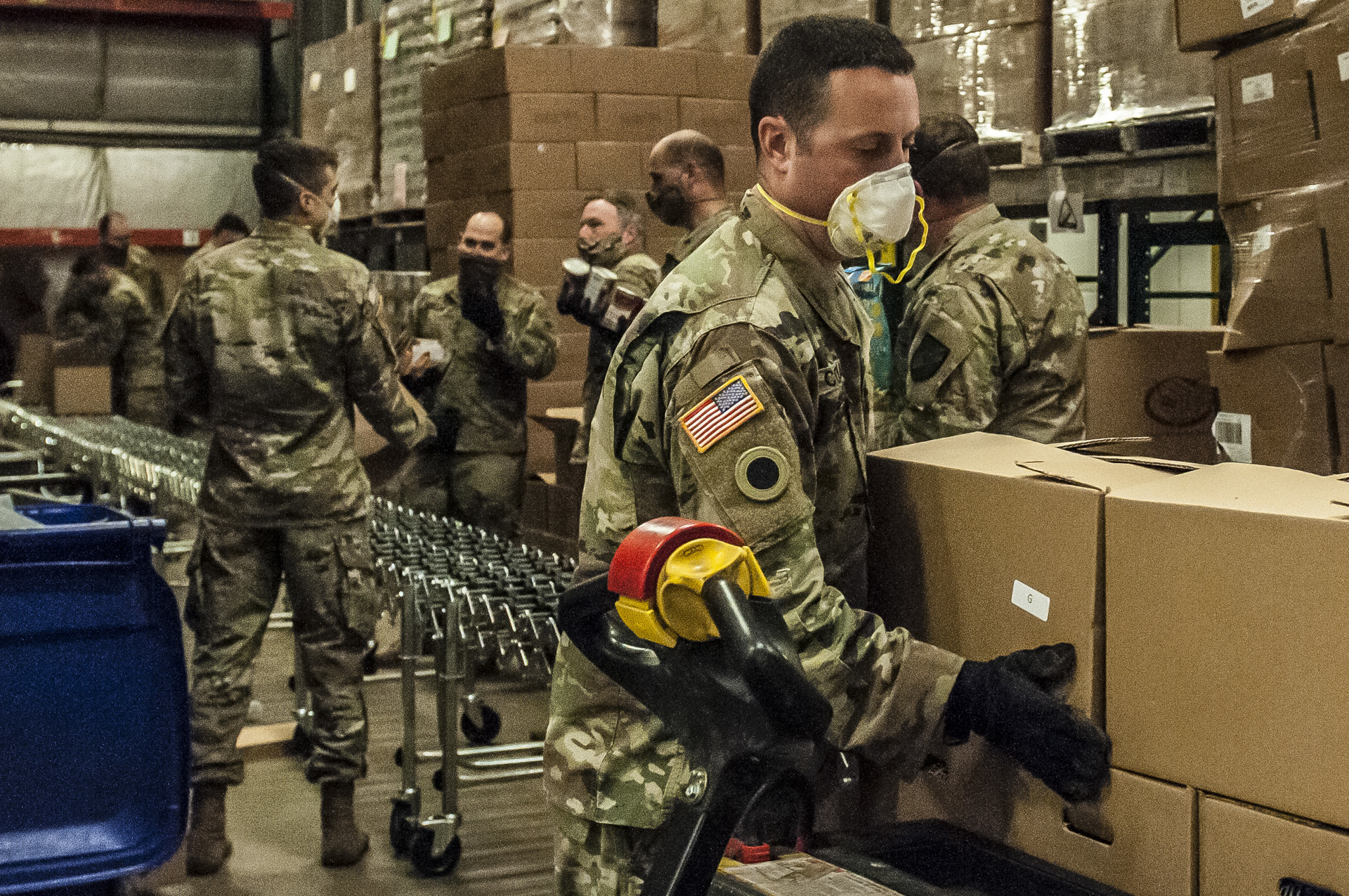 Soldiers pack boxes in assembly line.
