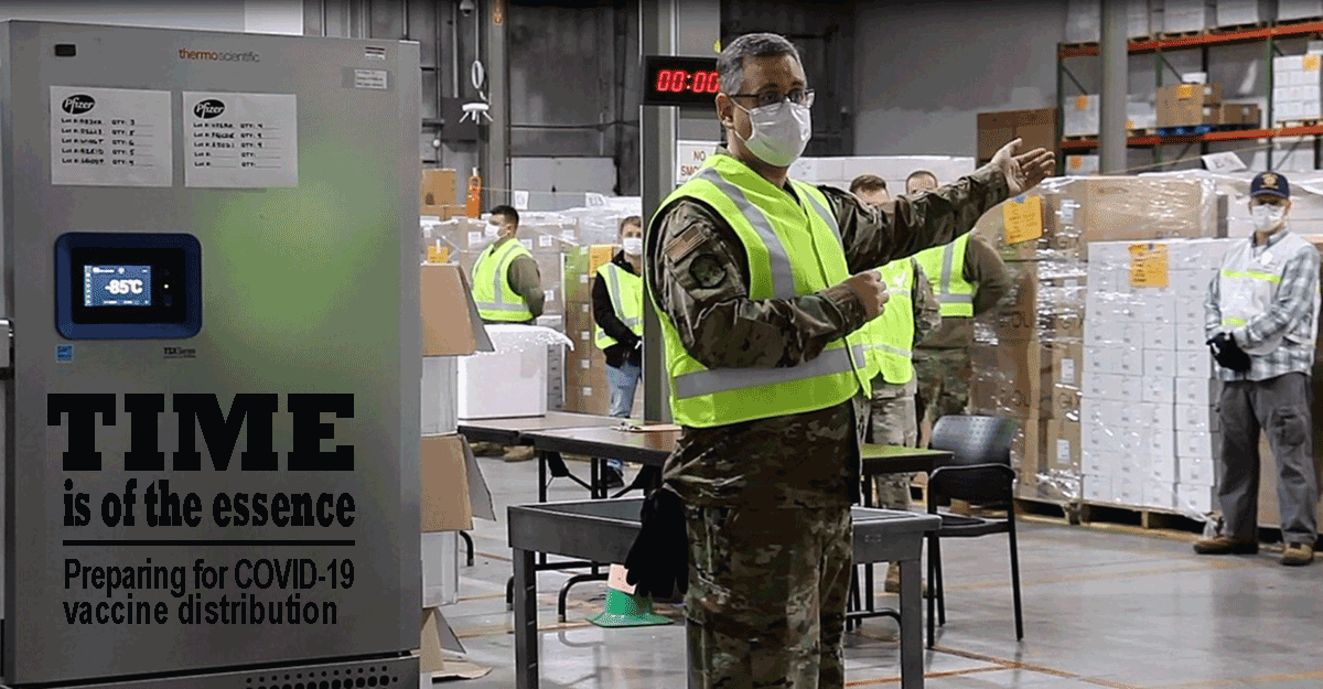 Soldier in uniform, yellow vest and mask, addresses others in warehouse.